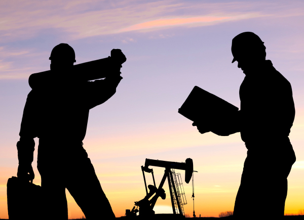 Silhouetted oil workers in front of a pump are probably wearing the latest nail fashion from skelzombie