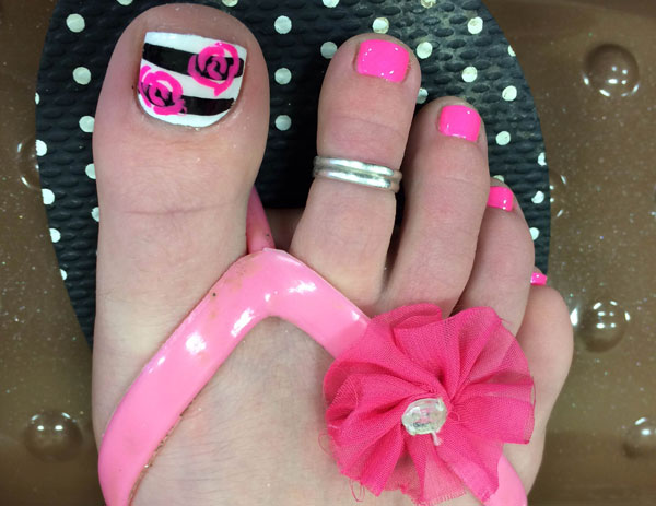 A woman's predominantly pink post-pedi look with nail art from Binh's Nails in Edmonton's East End