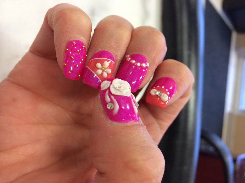 Fingernails painted pink with white 3D flowery features are available at Binh's