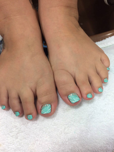 Painted toenails in robin's egg blue provide a stunning look from Binh's Nails in Edmonton
