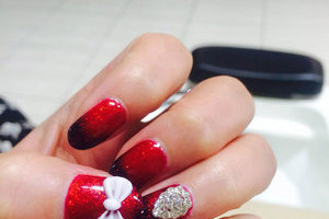 Blood red fingernails with glitter added, sets off the 3D gem and bow-tie flourishes in this exquisite Binh's Nails creation