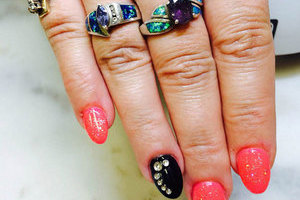 A female hand adorned with jewelrey that matches the 3D nail stylings applied by Binh's Nails artistic technicians