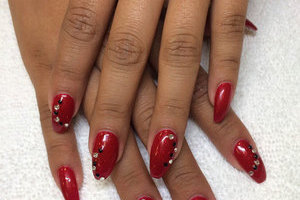 Womanly hands with deep red polish and gem elements produce a lovely look at Binh's Nails in Edmonton East