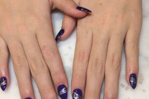 Lovely hands with deep purple polish host sparkling silver elements for a stunning finish from Binh's manicurists