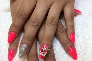 Feminine fingers with nails adorned with jewelled skulls, plain pink polish, and silver glitter is another Binh's Nails original