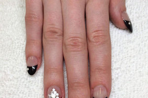 A woman's hand with dark nail tips and jewelled adornments create an alluring look from Binh's Nail Salon