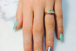 A lady's hand featuring nails in robins egg blue with the ring and index fingers in contrasting styles from Binh's manicures