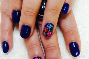 a pair of hands with shiny deep blue nails with fun floral features on the ring fingers from Binh's manicure artists
