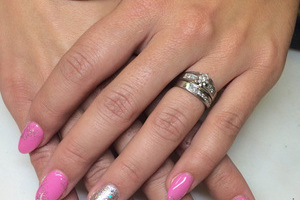 Pink polish with contrasting ring-finger hue and glitter makes an attractive presentation from Binh's Nail salon.