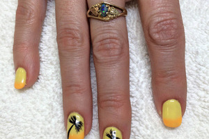 Fingernails painted yellow with tiny palm trees painted on the two middle fingers are a great finish from Salon Binh's in Edmonton