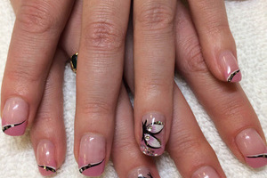 Female fingernails with clear polish and butterfly effects create a fun fashion statement from Binh's manicure salon in Edmonton