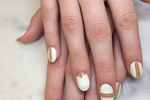 Stark white oval gel nails with a unique design in gold for every finger is a great style option from Binh's in East Edmonton.
