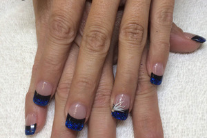 Feminine fingernails with clear polish, blue tips, glitter and white artistic touches on the ring fingers is a beautiful Binh's Nail design.