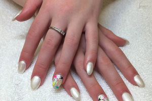 Smooth young hands with polished nails in white with Asian-inspired designs on the ring fingers from Binh's Nails