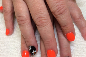 A woman's hands with orange polish on the nails and black polish with flowers on the ring fingers from Binh's