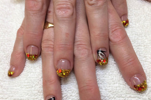 Female fingers decorated with gold tips and contrasting ring finger designs created by Binh's manicurists