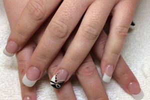 Feminine hands with French tips on the fingernails and styled design on the ring fingers is a terrific combination at Binh's manicures and pedicures.
