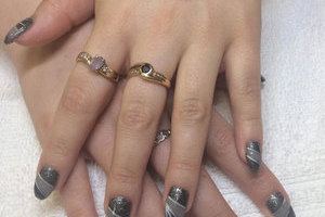 Tattooed female hands with oval gel nails in black, grey and glitter makes for a great look for younger clients.