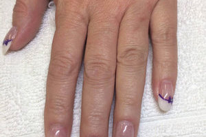 A feminine hand featuring oval nails with a matching bowtie motif is a great look available from Binh's Nails on 17 Street in Edmonton.