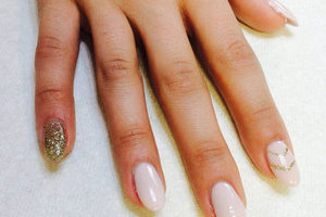 Oval gel nails in gleaming ivory with golden glitter accents present a powerful look from Binh's Nails in East Edmonton..