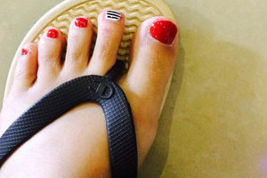 Shapely feet with red polish on four nails and B&W stripes on one from Binh's Salon.