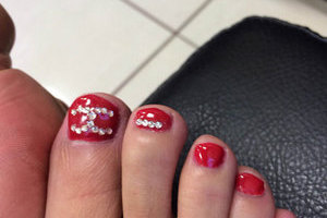 Red toenails with 3D jewel elements make a stunning fashion statement available at Binh's; the perfect place for a pedi