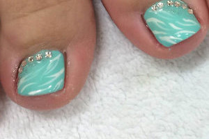 A pair of bare feet showing off turquoise toenails with glitter art accents from Binh's Nails pedicure pros.