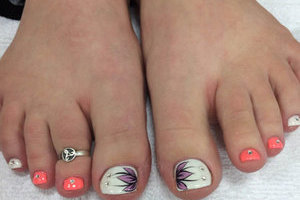 Feminine feet with various decorative touches on the toenails from the pedi artists at Binh's in Edmonton's east end