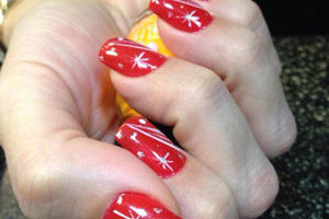 A lady's hand with squared gel nails featuring a blood red base with white accents from Binh's nail technicians