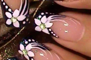 Light pink polished fingernails are expertly finished with black and white floral accents from Binh's