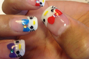 Fingernails bearing a kitten motif with different coloured bows create a spectacular style from Binh's manicures
