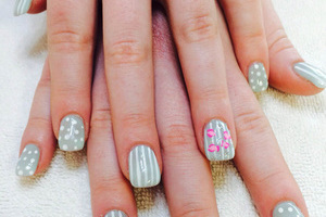 "Delicate fingers displaying polished nails in greys, whites and ""just been kissed"" designs at Binh's salon"