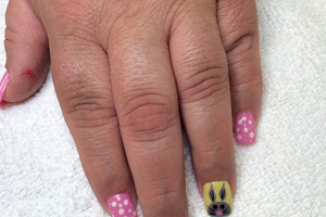 pink polished fingernails with white accents and a cartoon bunny on the ring finger by Binh's