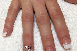 Polished fingernails in clear and white with flowered designs created by Binh's nail experts