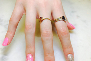Youthful-looking hands with pink nail polish and unique white flourishes on each finger