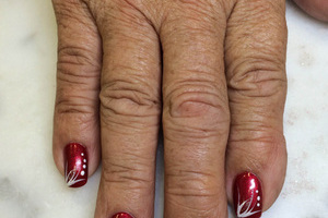Warm, red polish with a matching white design element on each finger looks lovely on this Binh's creation
