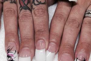 White nail polish on extra-long nails and design elements on the ring fingers makes a powerful statement at Binh's.