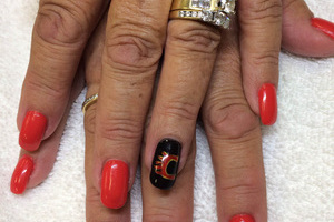 "The ""Flaming C"" is a stylish centerpiece of this hockey-themed manicure design from Binh's"