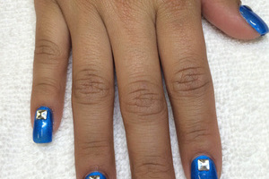 Shiny blue polish on square gels are accented with 3D design features at Binh's