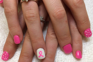 Pink nail polish is featured on these fingernails with a cancer ribbon motif created by Binh's
