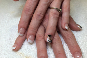 Binh's nails created this attractive manicure featuring French tips and black design elements for a lovely finsih