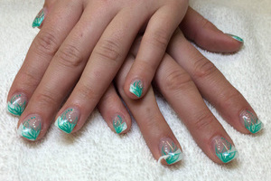 An ornate manicure featuring light green and white highlights created by the nail artisans at Binh's East