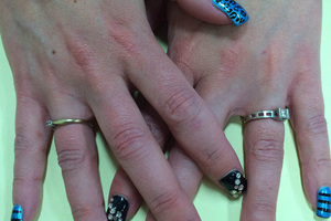 A striking Binh's manicure featuring black and jewel design elements against a blue blackground