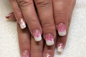 A woman displaying her manicure featuring pink glitter with white tips she received from the nail experts at Binh's.