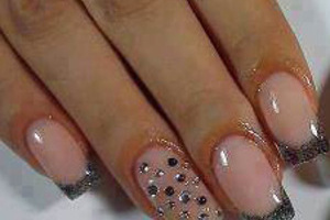 A lady's perfectly manicured fingernails featurimg glitter tips on a square gel platform from Binh's on 17 Street