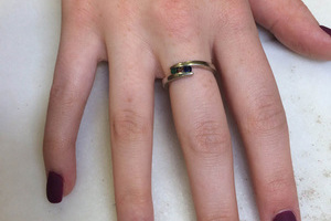 A single female hand highlighted by dark purple polish from the nail stylists at Binh's.