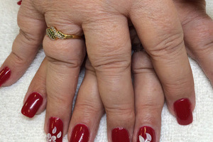A woman's fingers stylized with deep red polish and white flower appliques from Binh's on 17th Street