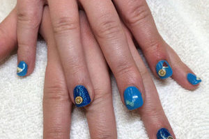 A pair of hands with squared nails in light and dark blue with sailing imagery creates a unique style from Binh's in Edmonton