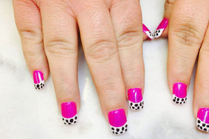Female hands featuring painted nails in pink with spotted dalmation-print highlights is just one of the many style options available from Binh's Nails in Edmonton