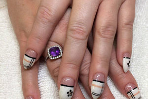 Hands with painted nails in white with black accents create a lovely style at Binh's manicures